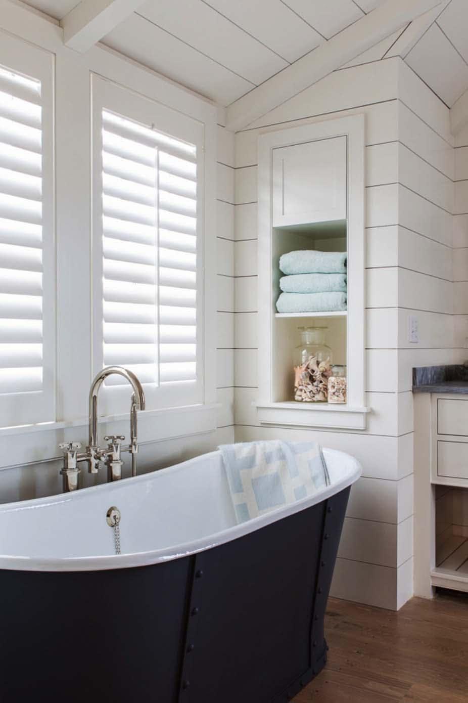 White plantation shutters on bathroom window next to bathtub