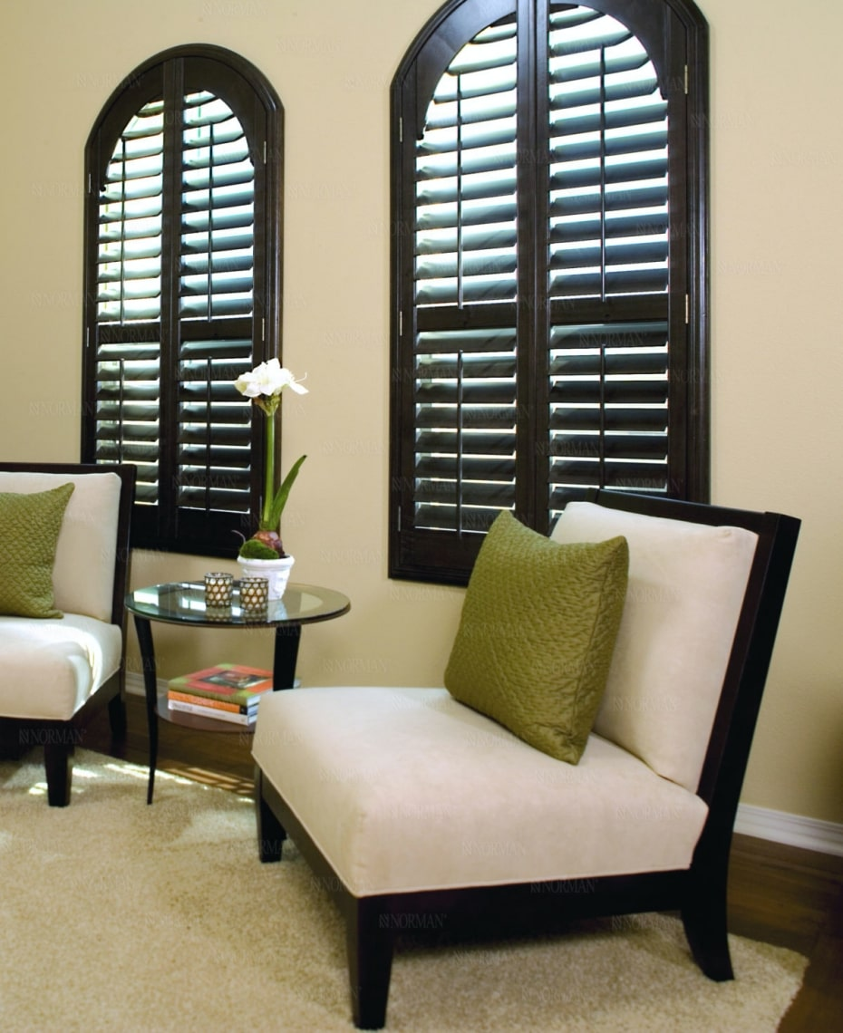 Custom plantation shutters with dark wood and top arch