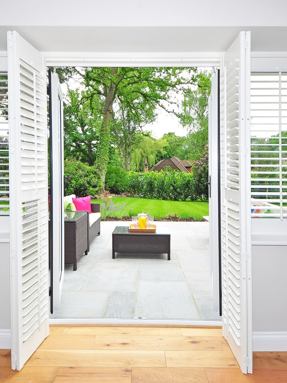 Plantation shutters with view of patio and trees outside